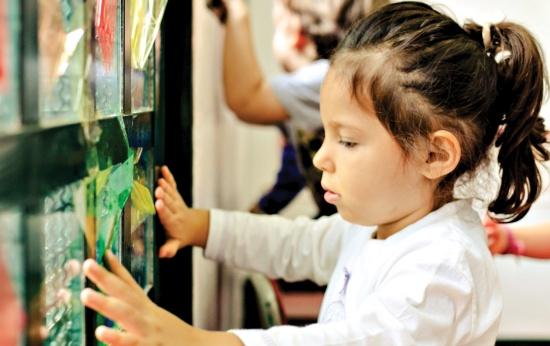 Menina observa vitrais feitos com papel celofone e vidro