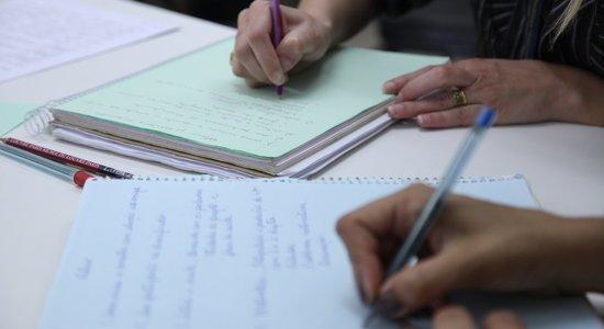 Duas professoras escrevem relatórios em cima de uma mesa. Na foto, só aparecerem as mãos das mulheres e os cadernos (Foto: Gabriela Portilho)