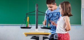 Crianças verificam balança com pequenos pesos em sala de aula