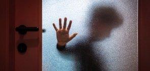 Pessoa atrás de uma porta de vidro embaçada