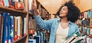 Mulher segura livros e escolhe outro livro na prateleira