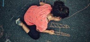 Uma menina de cerca de 7 anos desenhando com giz no asfalto. A menina é vista de cima e o desenho que ela faz é parecido com um H