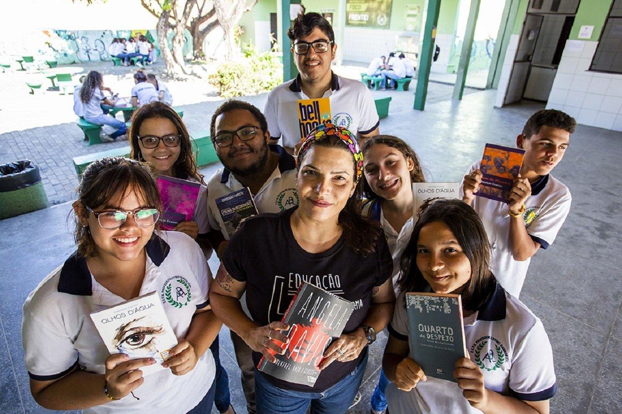 A professora Camile Baccin de Moura e os alunos da EEFM Aloysio Barros Leal mostram os livros pesquisados