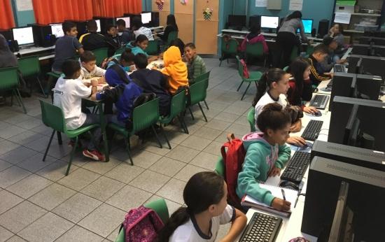 Sala de aula com alunos utilizando o computador e outros realizando uma atividade na mesa. Crédito: Debora Garofalo