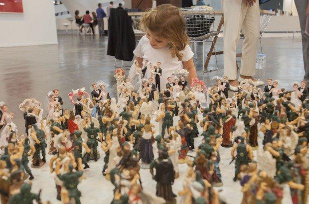 Garotinha observa escultura com soldadinhos de chuva | Crédito: Divulgação