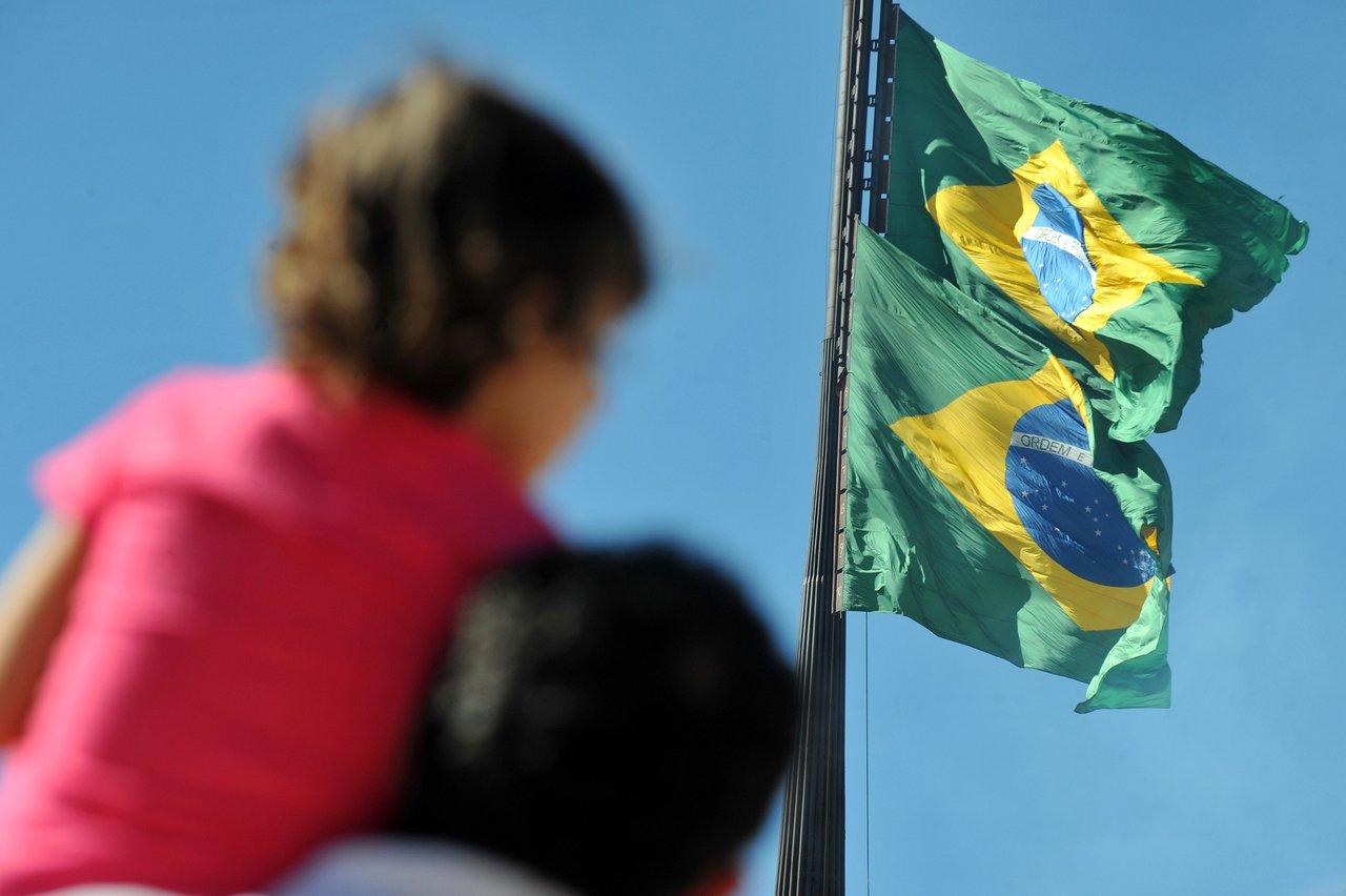 Pai segura menino nos ombros durante comemoração cívica com duas bandeiras do Brasil gigantes hasteadas ao fundo