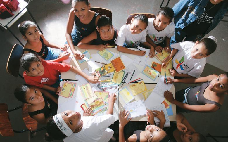Jovens leitores escrevem cartões-postais numa atividade do projeto Letras de Luz: mais de 2 mil agentes culturais capacitados em 51 cidades. Foto: Silvia Zamboni