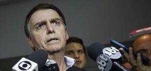 Um homem branco de cerca de 50 anos falando ao microfone de emissoras de TV como Globo e SBT