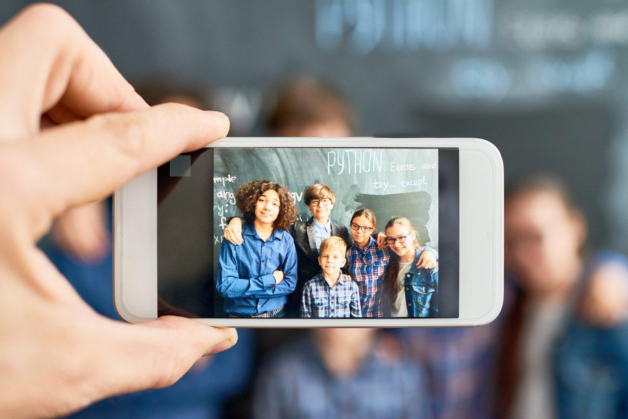 Celular enquadra alunos em sala de aula, em frente a uma lousa verde, para uma foto
