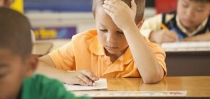Um menino de cerca de 8 anos segurando a cabeça enquanto faz uma prova