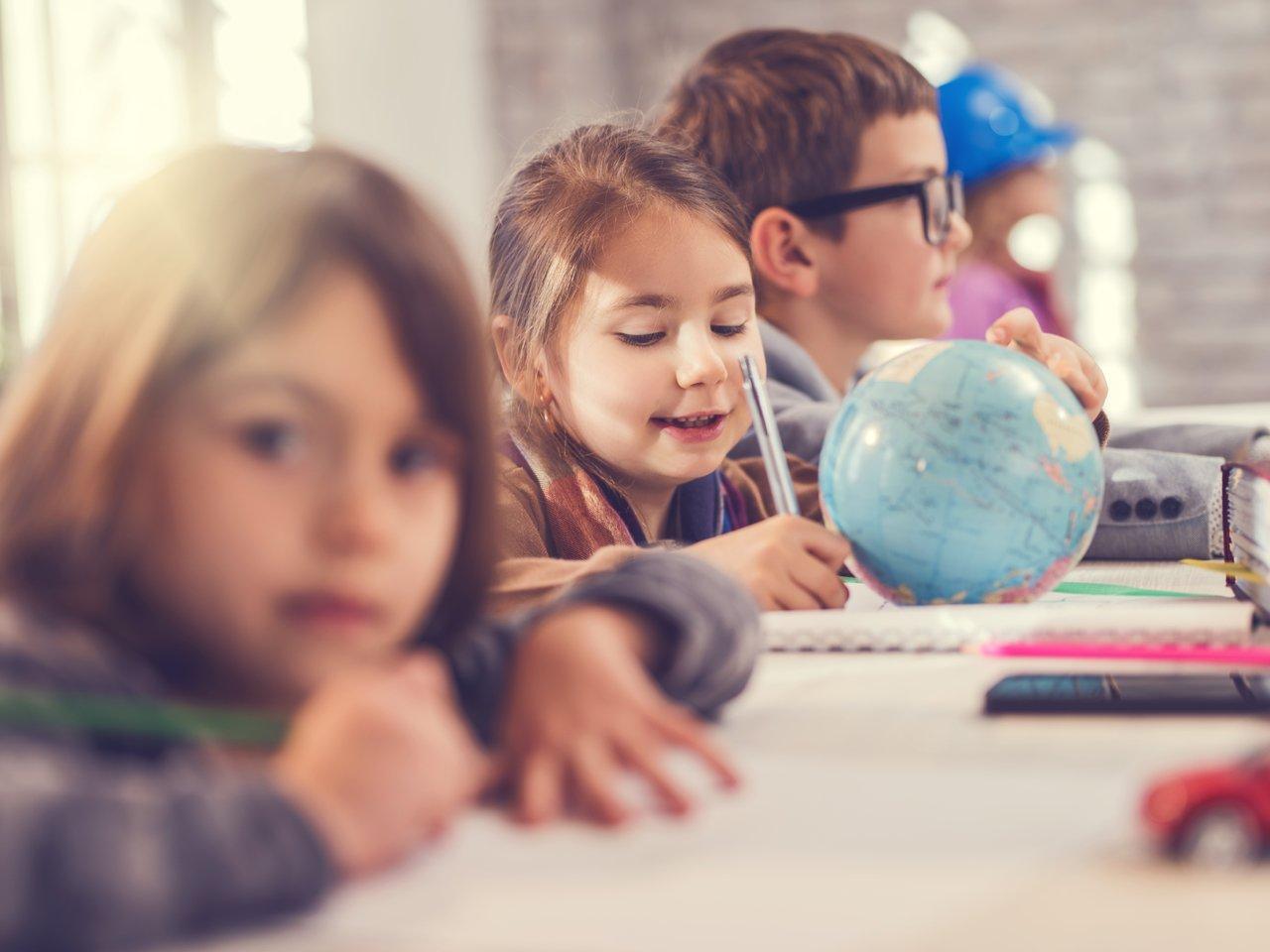 Menina escreve em uma mesa junto com outras crianças tendo um pequeno globo terrestre à sua frente