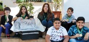 Foto de cinco alunos e uma professora sentados na escada. Ao lado deles, está o forno construido
