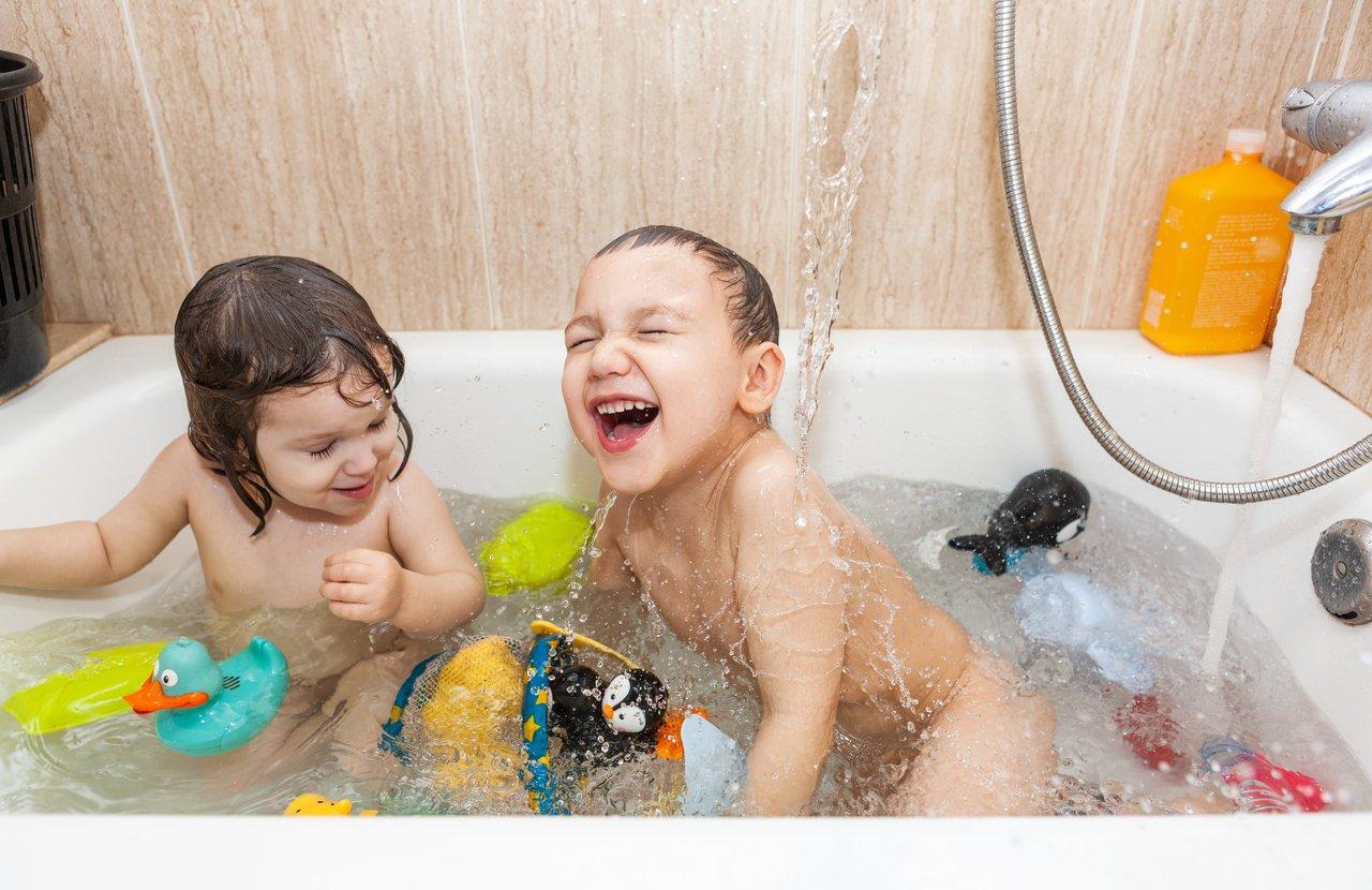 Uma menina e um menino brincam em uma banheira cheia de água e de brinquedos