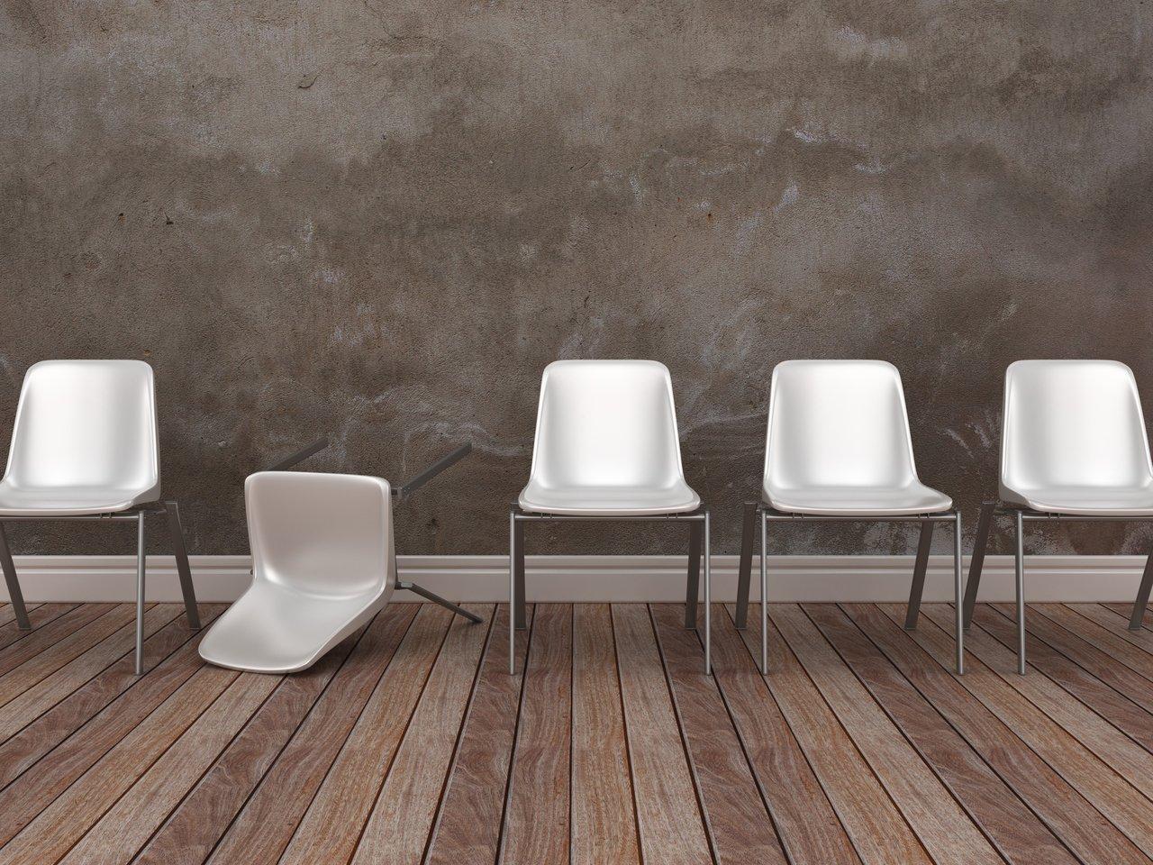 Cadeira branca caída em meio à fileira com outras cadeiras, em uma sala com piso de madeira e parede de concreto
