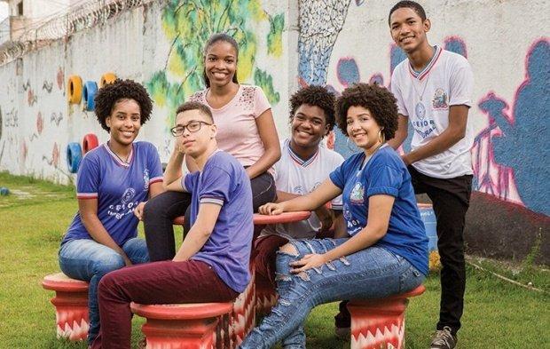 Ao ar livre, 6 jovens sentam em roda e sorriem