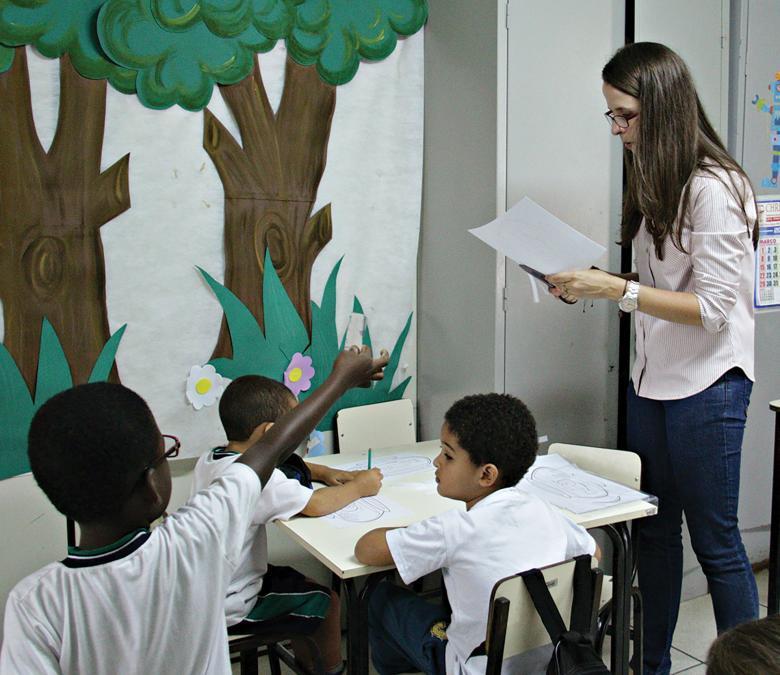 Professora em momento de aula recortando um papel