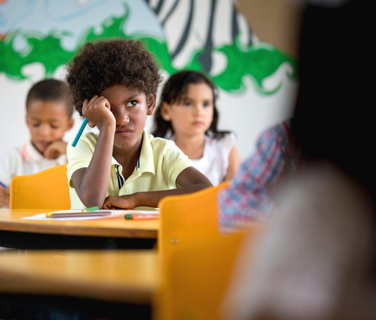 Aluno com expressão de descontentamento, sentado em uma carteira em uma escola, segura um lápis azul e olha para a professora