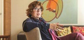 Mulher branca com cabelo curto cor mel, usa óculos, está sentada em uma poltrona conversando