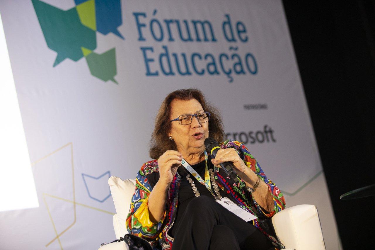 Sentada em uma cadeira, no palco do Fórum de Educação, a escritora Ana Maria Machado gesticula e conversa com a plateia