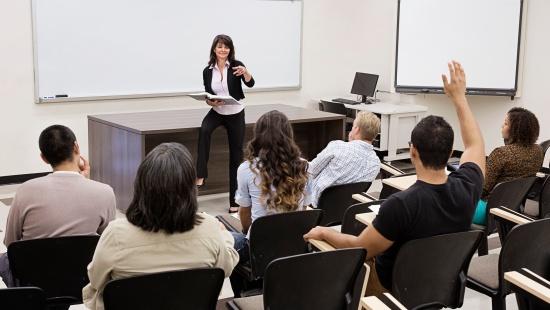 Professora sentada em sua mesa conversando com estudantes universitários sentados em carteiras dispostas em fila. O grupo é misturado entre mulheres e homens