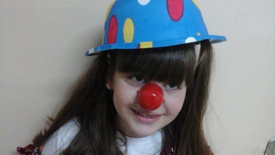 menina branca de longos cabelos castanhos e lisos e franja sorri vestindo um chapéu colorido (azul com bolas rosas) e nariz de palhaço