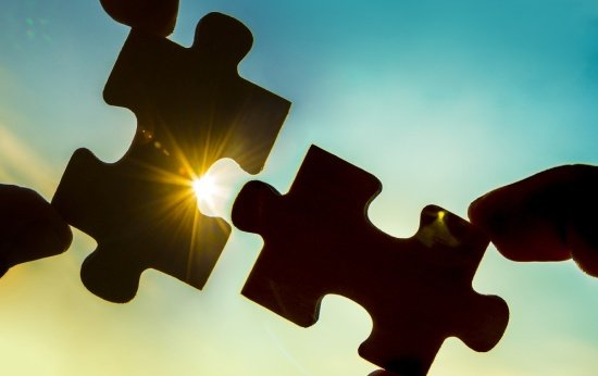 Duas peças de quebra-cabeça se encaixando contra a luz do sol
