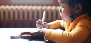 criança escrevendo em mesa