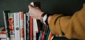Cerca de 10 livros lado a lado e uma mão de mulher retirando um deles