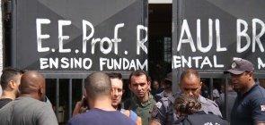Policiais são vistos diante do portão de entrada da Escola Estadual Professor Raul Brasil, em Suzano, onde dois jovens mataram estudantes e funcionários antes de cometer suicídio