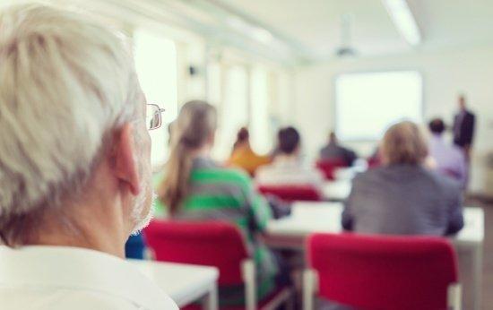 Sala de aula vista do fundo. Só uma das cabeças que aparecem está focada e é de uma pessoa idosa, de cabelos brancos. O resto da turma está desfocada.