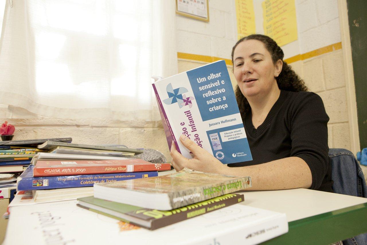 """A professora Mara Mansani está sentada numa mesa de sala de aula e lê um livro chamado """"Um olhar sensível e reflexão sobre a criança"""" (Crédito: Mariana Pekin)"""