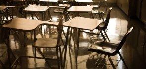 Sala de aula com várias carteiras vazias dispostas em fila
