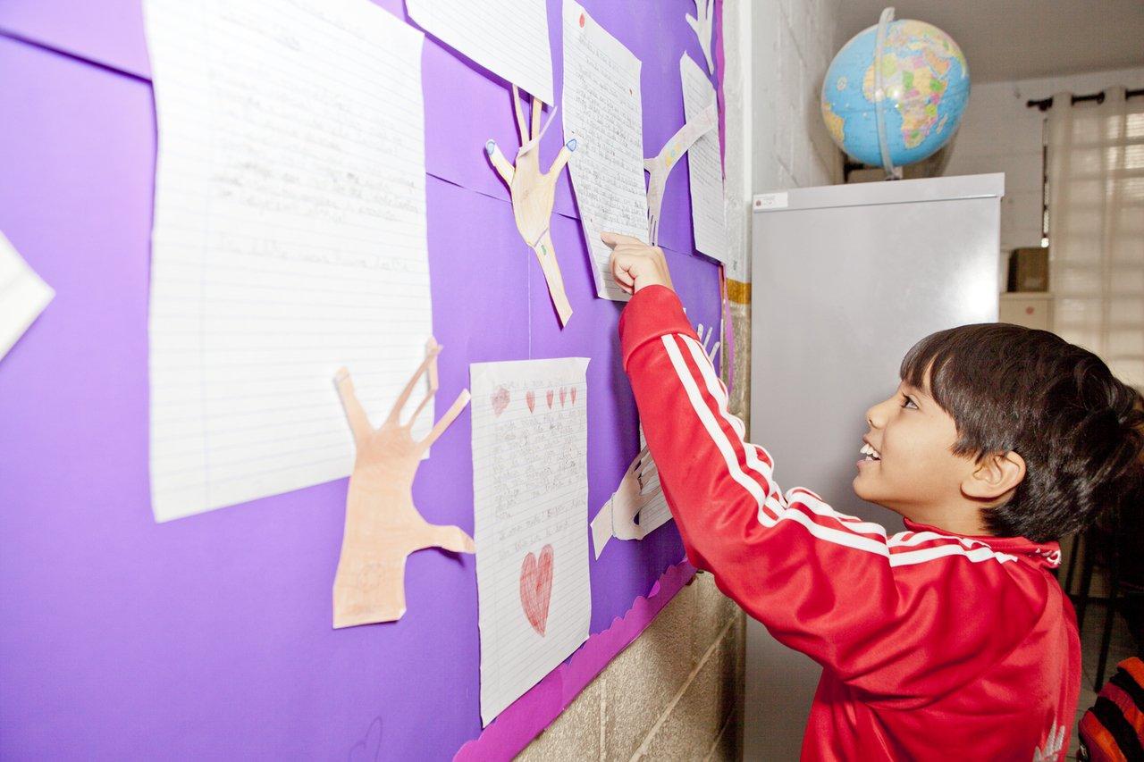 O aluno Isaac lê textos produzidos pela turma, no mural da sala de aula