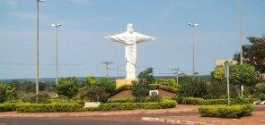 Foto da entrada da cidade, há uma pequena estátua do cristo redentor