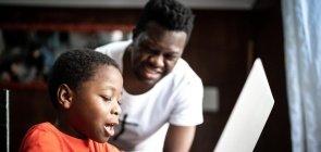 Como trabalhar os gêneros textuais digitais?_ menino estudando em casa com o pai