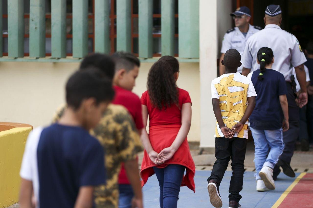 Crianças de costas para a câmera caminham para a entrada da escola no CED 01 da Estrutural, uma das escolas públicas do DF onde foi implementado o modelo cívico-militar. Policiais militares observam a entrada na porta