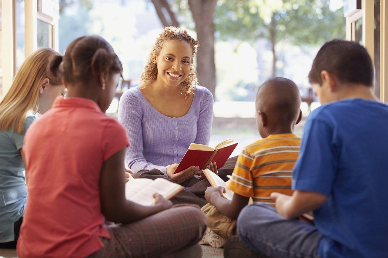 Professora sorrindo em sala de aula com livro em mãos cercada por alunos
