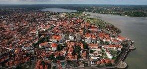 Vista aérea da cidade de São Luís, no Estado do Maranhão, com muitos prédios, casas e um grande rio.