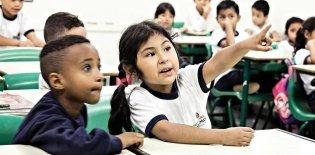 Um menino negro ao lado de uma menina japonesa em uma sala de aula. A menina aponta para frente como quem mostra algo, enquanto o menino observa atento