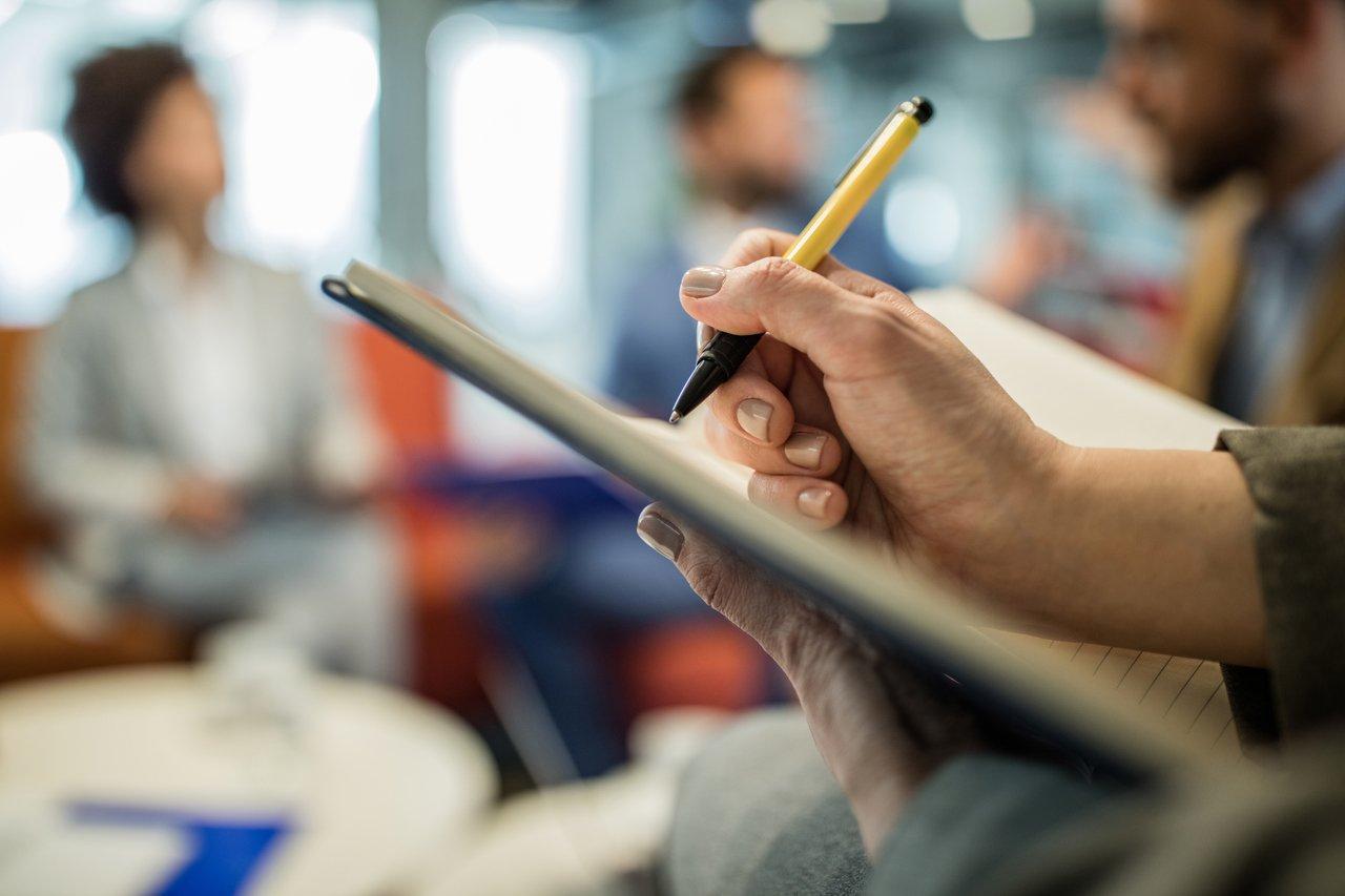 Pessoa escreve em um caderno de capa dura preta com pessoas desfocadas ao fundo
