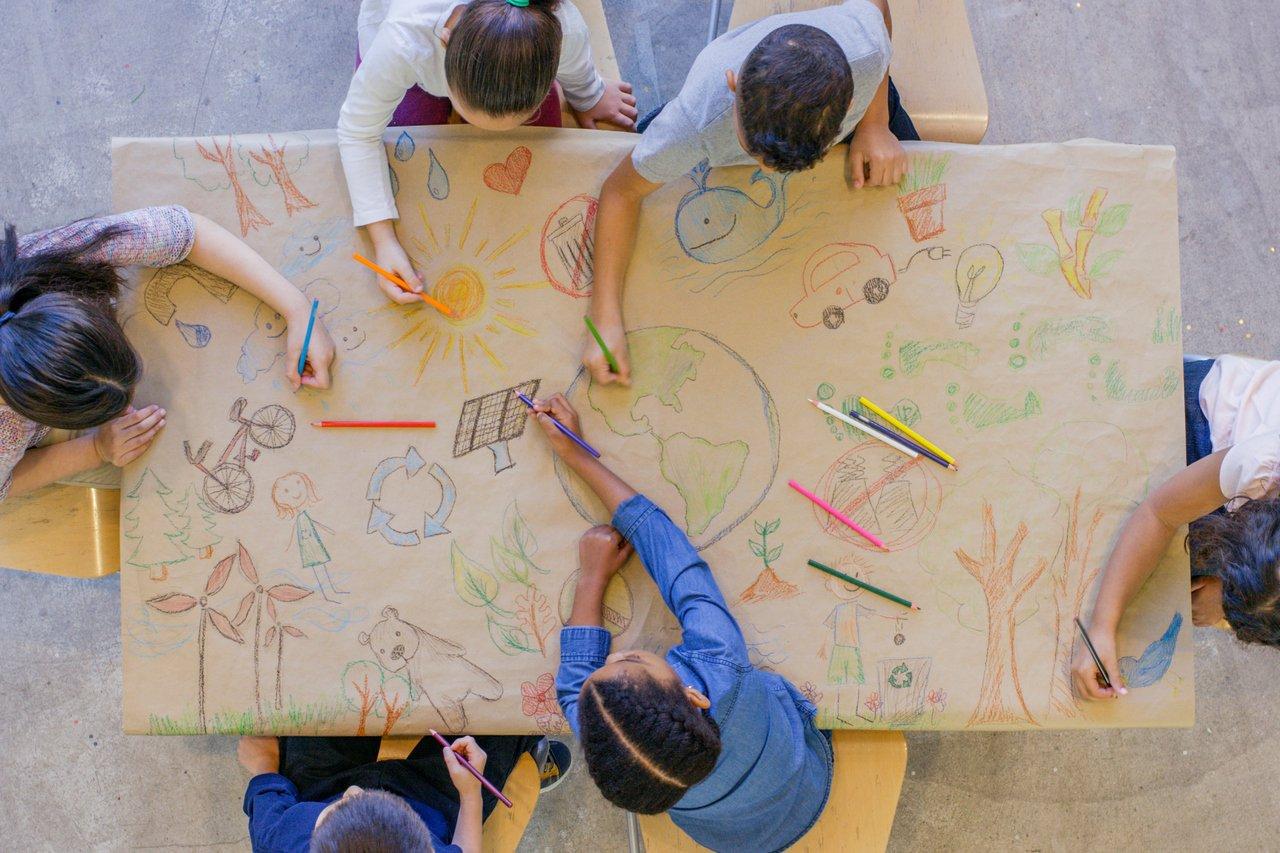 Crianças desenham juntas em sala de aula