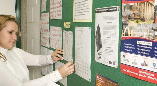 Mulher prega informes em mural na escola (Foto: Divulgação)