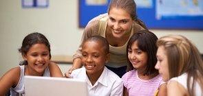 Professora com alunos diante do computador na sala de aula