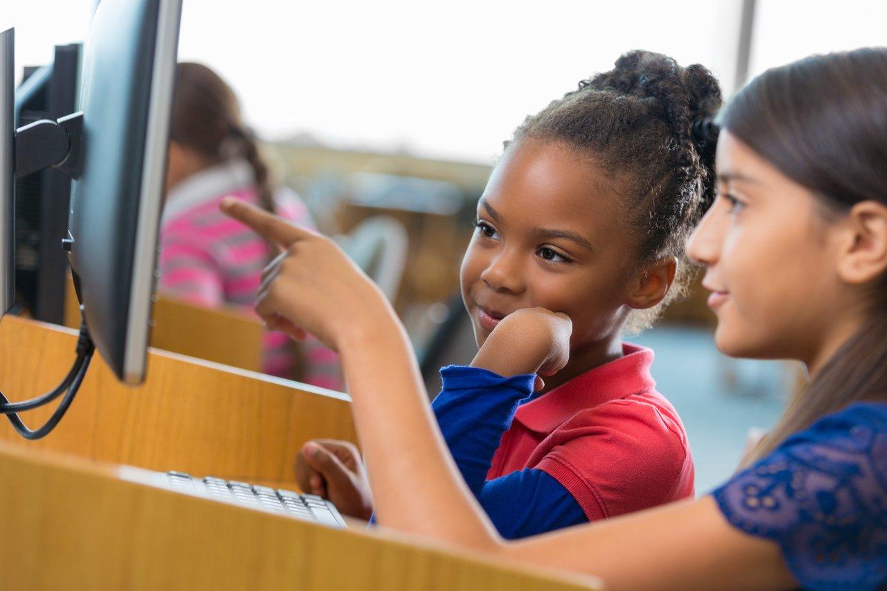 Duas meninas em frente a um computador, uma delas aponta para a tela e a outra sorri