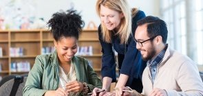 Professores conversam sobre documentos ao redor da mesa