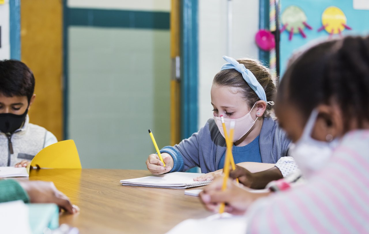 colegas de classe no ensino fundamental usando máscaras faciais