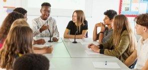alunos debatem sentados em mesa