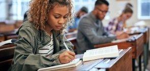 uma mulher de cerca de 20 anos em uma sala de aula escrevendo no caderno. sobre sua mesa também há um livro