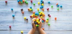 Criança segura balas coloridas