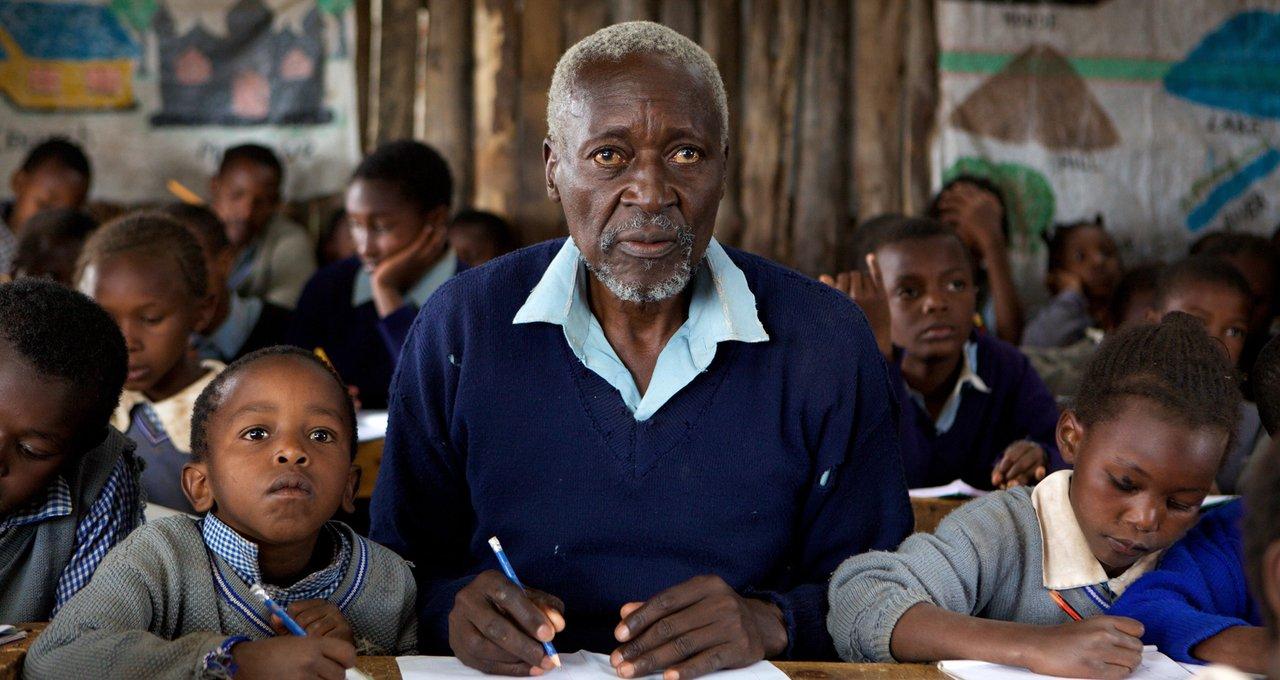 Homem de meia idade e duas crianças ao seu lado dentro de uma criança dentro de uma sala de aula